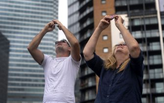 Local residents take pictures of the partial solar eclipse over Canary Wharf in London. Picture date: Thursday June 10, 2021.
