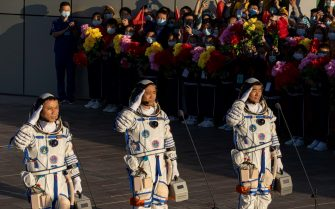 epa09278425 Chinese astronauts (L-R) Tang Hongbo, Nie Haisheng, and Liu Boming salute during a departure ceremony before the launch of the Long March-2F carrier rocket, carrying the Shenzhou-12 at the Jiuquan Satellite Launch Center, in the Gobi Desert, northwest of China, 17 June 2021. China launches Shenzhou-12 spacecraft carrying three crew members Tang Hongbo, Nie Haisheng, and Liu Boming to the orbiting Tianhe core module for a three-month mission on 17 June. It is the first spaceflight in almost five years where China sends humans into space.  EPA/ROMAN PILIPEY