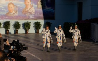 epa09278422 Chinese astronauts (L-R) Tang Hongbo, Nie Haisheng, and Liu Boming wave during a departure ceremony before the launch of the Long March-2F carrier rocket, carrying the Shenzhou-12 at the Jiuquan Satellite Launch Center, in the Gobi Desert, northwest of China, 17 June 2021. China launches Shenzhou-12 spacecraft carrying three crew members Tang Hongbo, Nie Haisheng, and Liu Boming to the orbiting Tianhe core module for a three-month mission on 17 June. It is the first spaceflight in almost five years where China sends humans into space.  EPA/ROMAN PILIPEY