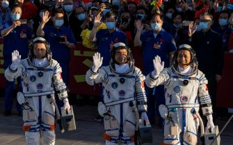 epa09278427 Chinese astronauts Tang Hongbo, Nie Haisheng, and Liu Boming wave during a departure ceremony before the launch of the Long March-2F carrier rocket, carrying the Shenzhou-12 at the Jiuquan Satellite Launch Center, in the Gobi Desert, northwest of China, 17 June 2021. China launches Shenzhou-12 spacecraft carrying three crew members Tang Hongbo, Nie Haisheng, and Liu Boming to the orbiting Tianhe core module for a three-month mission on 17 June. It is the first spaceflight in almost five years where China sends humans into space.  EPA/ROMAN PILIPEY