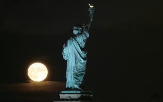 JERSEY CITY, NJ - AUGUST 22: The full Sturgeon Blue Moon rises next to the Statue of Liberty in New York City on August 22, 2021 as seen from Jersey City, New Jersey. (Photo by Gary Hershorn/Getty Images)