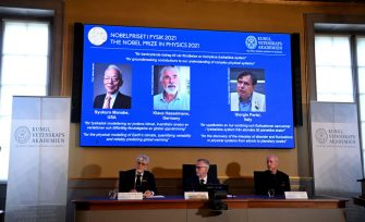 Goran K. Hansson (C), Secretary General of the Royal Swedish Academy of Sciences, and members of the Nobel Committee for Physics Thors Hans Hansson (L) and John Wettlaufer (R) sit in front of a screen displaying the co-winners of the 2021 Nobel Prize in Physics (L-R) Syukuro Manabe (US-Japan), Klaus Hasselmann (Germany) and Giorgio Parisi (Italy) at the Royal Swedish Academy of Sciences in Stockholm, Sweden, on October 5, 2021. - US-Japanese scientist Syukuro Manabe, Klaus Hasselmann of Germany and Giorgio Parisi of Italy won the Nobel Physics Prize for climate models and the understanding of physical systems, the jury said. Manabe and Hasselmann share one half of the prize for their research on climate models, while Parisi won the other half for his work on the interplay of disorder and fluctuations in physical systems. (Photo by Jonathan NACKSTRAND / AFP) (Photo by JONATHAN NACKSTRAND/AFP via Getty Images)