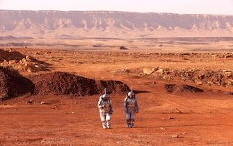 """Due """"astronauti"""" camminano in un'area del deserto del Negev, in Israele, durante la simulazione di una missione su Marte"""