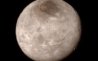 IN SPACE - JULY 13:  In this handout provided by the National Aeronautics and Space Administration (NASA), Pluto's largest moon Charon is shown from a distance of 289,000 miles (466,000 kilometers) from the Long Range Reconnaissance Imager (LORRI) aboard NASA's New Horizons spacecraft, taken on July 13, and released July 15, 2015. New Horizons passed by Pluto July 14, closing to a distance of about 7,800 miles (12,500 kilometers). The image was combined with color information taken from the craft's Ralph instrument. The 1,050-pound piano sized probe was launched January 19, 2006 aboard an Atlas V rocket from Cape Canaveral, Florida, (Photo by NASA/APL/SwRI via Getty Images)