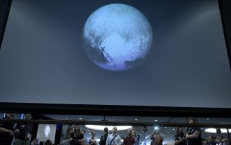 People look at an early image of Pluto taken by NASA's New Horizons probe as the craft makes its closest fly-by of the dwarf planet at the Johns Hopkins University Applied Physics Laboratory July 14, 2015 in Laurel, Maryland. The unmanned NASA spacecraft whizzed by Pluto on JUly 14, making its closest approach in the climax of a decade-long journey to explore the dwarf planet for the first time, the US space agency said. Moving faster than any spacecraft ever built -- at a speed of about 30,800 miles per hour (49,570 kph) -- the flyby happened at 7:49 am (1149 GMT), with the probe running on auto-pilot. It was to pass by Pluto at a distance of 7,767 miles (12,500 kilometers). AFP PHOTO/BRENDAN SMIALOWSKI        (Photo credit should read BRENDAN SMIALOWSKI/AFP via Getty Images)