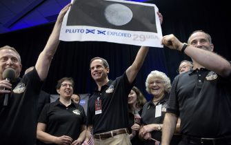 Dr. Allan Stern (L), principal investigator for the New Horizons mission to Pluto, and others hold up their suggestion for a modified US Post Office stamp of Pluto at the Johns Hopkins University Applied Physics Laboratory to celebrate the closest fly-by of the New Horizons probe July 14, 2015 in Laurel, Maryland. The unmanned NASA spacecraft whizzed by Pluto on JUly 14, making its closest approach in the climax of a decade-long journey to explore the dwarf planet for the first time, the US space agency said. Moving faster than any spacecraft ever built -- at a speed of about 30,800 miles per hour (49,570 kph) -- the flyby happened at 7:49 am (1149 GMT), with the probe running on auto-pilot. It was to pass by Pluto at a distance of 7,767 miles (12,500 kilometers). Looking on 2nd-Right is Annette Tombaugh, daughter of the man who discovered Pluto, Clyde Tombaugh. AFP PHOTO/BRENDAN SMIALOWSKI        (Photo credit should read BRENDAN SMIALOWSKI/AFP via Getty Images)