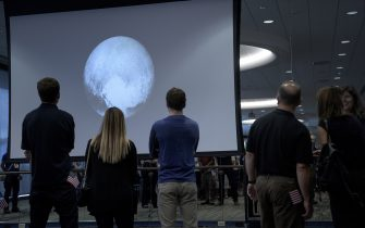 People look at an early image of Pluto taken by the New Horizons probe as the craft makes its closest fly-by of the dwarf planet at the Johns Hopkins University Applied Physics Laboratory July 14, 2015 in Laurel, Maryland. The unmanned NASA spacecraft whizzed by Pluto on July 14, making its closest approach in the climax of a decade-long journey to explore the dwarf planet for the first time, the US space agency said. Moving faster than any spacecraft ever built -- at a speed of about 30,800 miles per hour (49,570 kph) -- the flyby happened at 7:49 am (1149 GMT), with the probe running on auto-pilot. It was to pass by Pluto at a distance of 7,767 miles (12,500 kilometers). AFP PHOTO/BRENDAN SMIALOWSKI        (Photo credit should read BRENDAN SMIALOWSKI/AFP via Getty Images)