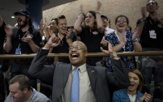 NASA and project staff react with others as telemetry is received from the New Horizons probe at the Johns Hopkins University Applied Physics Laboratory in Laurel, Maryland on July 14, 2015. The New Horizons interplanetary space probe reestablished contact with NASA after safe passage completing its closest approach fly-by of Pluto making the United States the first to explore the dwarf planet. AFP PHOTO/BRENDAN SMIALOWSKI        (Photo credit should read BRENDAN SMIALOWSKI/AFP via Getty Images)