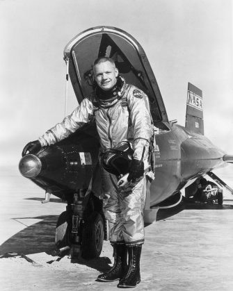 1966:  Full-length portrait of American astronaut Neil Armstrong, wearing a NASA spacesuit, smiling while standing with his hand on the 'hot nose' of an X-15 shuttle on a tarmac. The 'hot nose' is an invention which senses the X-15's alitude angles and compensates to lessen the frictional heat during the exit and re-entry phases of hypersonic flight in the upper atmoshere.  (Photo by Hulton Archive/Getty Images)