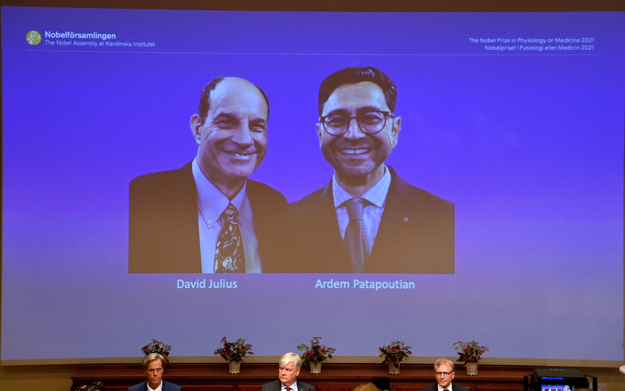 Members of the Nobel Committee sit in front of a screen displaying the winners of the 2021 Nobel Prize in Physiology or Medicine David Julius (L) and Ardem Patapoutian, during a press conference at the Karolinska Institute in Stockholm, Sweden, on October 4, 2021. - US scientists David Julius and Ardem Patapoutian won the Nobel Medicine Prize for discoveries on receptors for temperature and touch. (Photo by Jonathan NACKSTRAND / AFP) (Photo by JONATHAN NACKSTRAND/AFP via Getty Images)