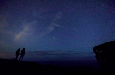 """TOPSHOT - This picture taken on August 12, 2017 shows a couple enjoying Perseid meteor along the Milky Way illuminating the dark sky near Comillas, Cantabria community, northern Spain, during the """"Perseids"""" meteor shower. - Northern hemisphere sky-gazers are in for a special treat on August 11 and 13, night with a rare shooting star """"outburst"""", which astronomers hope will not be marred by clouds and a bright Moon. (Photo by CESAR MANSO / AFP)        (Photo credit should read CESAR MANSO/AFP via Getty Images)"""