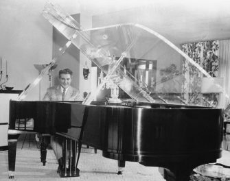 (Original Caption) Piano with a View. Hollywood: Ivory idol Liberace tries out his new $10,000 Baldwin Concert Grand which features a clear plastic lid. The unique top enables the popular TV pianist to see, and be seen by, guests for whom he plays in his Hollywood home.