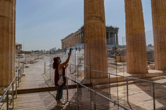 A worker wearing a protective mask cleans a divider made of plexiglass at the entrance of the Acropolis in Athens on May 18, 2020 amid the pandemic of the novel coronavirus (COVID-19). - Greece reopened the Acropolis in Athens and all open-air archaeological sites in the country to the public on May 11 after a two-month closure due to the coronavirus pandemic. (Photo by Aris MESSINIS / AFP) (Photo by ARIS MESSINIS/AFP via Getty Images)