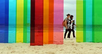 Two beachcombers walk past the perspex work 'A Symbolic Inscription of the Imaginary' by Australian artist Nicholas Elias during the official launch of the 13th Sculpture By The Sea exhibition on Sydney's Tamarama Beach on October 29, 2009. The annual outdoor display features sculptures by 114 Australian and international artists and is expected to attract over 600,000 visitors before closing on November 15.  AFP PHOTO/Torsten BLACKWOOD (Photo credit should read TORSTEN BLACKWOOD/AFP via Getty Images)