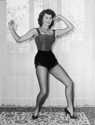 circa 1960:  Full-length view of Italian actor Sophia Loren posing in a cabaret costume with fishnet stockings and high heels in front of a window.  (Photo by Nino Serafini/Hulton Archive/Getty Images)