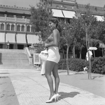 American actress and singer Abbe Lane, wearing a swimming bra and a high-waisted hot pants, holding a handbag, standing on the path of the Excelsior Hotel, Lido, Venice 1954. (Photo by Archivio Cameraphoto Epoche/Getty Images)