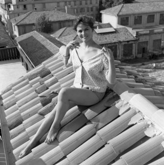 Italian actress Claudia Cardinale sitting on the roof top, wearing hotpants, a shirt and some bangles, baring her shoulders, Rome, 1958. (Photo by Archivio Cameraphoto Epoche/Getty Images)
