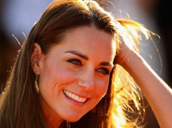 AYERS ROCK, AUSTRALIA - APRIL 22:  Catherine, Duchess of Cambridge touches her hair as she smiles after walking down Kuniya Walk at the base of Uluru on April 22, 2014 in Ayers Rock, Australia. The Duke and Duchess of Cambridge are on a three-week tour of Australia and New Zealand, the first official trip overseas with their son, Prince George of Cambridge.  (Photo by Scott Barbour/Getty Images)