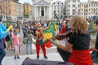 Una violinista suona un brano, mentre alcuni ragazzi danzano, durante la manifestazione dei lavoratori dello spettacolo organizzata davanti alla stazione ferroviaria di Venezia, 30 maggio 2020. Alla protesta pacifica ha aderito un migliaio di persone. ANSA/ANDREA MEROLA