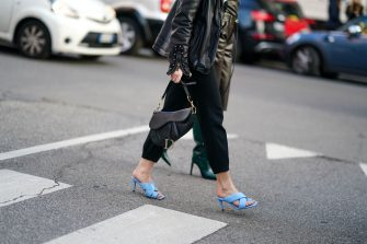 MILAN, ITALY - FEBRUARY 22: A guest wears a black leather jacket, black crop pants, a black Dior saddle bag, blue heeled sandals, outside Bottega Veneta, during Milan Fashion Week Fall/Winter 2020-2021 on February 22, 2020 in Milan, Italy. (Photo by Edward Berthelot/Getty Images)