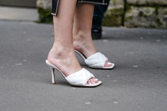PARIS, FRANCE - FEBRUARY 28: A guest wears white quilted sandals shoes, outside Nina Ricci, during Paris Fashion Week - Womenswear Fall/Winter 2020/2021, on February 28, 2020 in Paris, France. (Photo by Edward Berthelot/Getty Images)