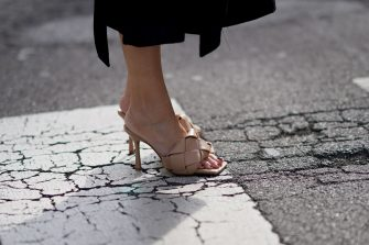 MILAN, ITALY - FEBRUARY 21: A guest wears pale brown woven leather Bottega Veneta sandals shoes, outside Sportmax, during Milan Fashion Week Fall/Winter 2020-2021 on February 21, 2020 in Milan, Italy. (Photo by Edward Berthelot/Getty Images)