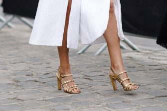 PARIS, FRANCE - MAY 03: A guest wears a white tweed divided skirt, shiny golden bejewelled heeled sandals, outside the Chanel Cruise Collection 2020  At Grand Palais on May 03, 2019 in Paris, France. (Photo by Edward Berthelot/Getty Images )