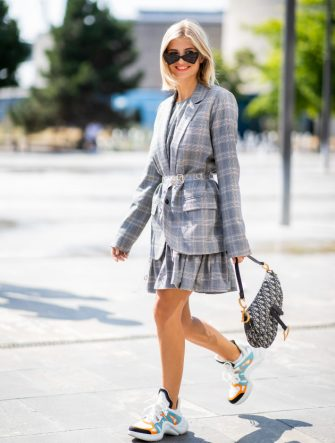 COPENHAGEN, DENMARK - AUGUST 09: Xenia Adonts wearing Louis Vuitton sneakers, Dior saddle bag, grey checked belted jacket is seen outside Designers Remix during the Copenhagen Fashion Week Spring/Summer 2019 on August 9, 2018 in Copenhagen, Denmark. (Photo by Christian Vierig/Getty Images)