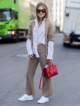 OSLO, NORWAY - AUGUST 22: Gine Margrethe wearing light brown suit, red Saint Laurent bag, striped button shirt, white sneakers outside byTiMo on August 22, 2017 in Oslo, Norway. (Photo by Christian Vierig/Getty Images)
