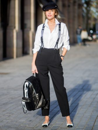 BARCELONA, SPAIN - NOVEMBER 27: Alexandra Lapp  wearing black and white vintage Chanel suspenders with Chanel logo in black and white, a white oversized shirt from Steffen Schraut, black high waist pants from Zara, XL backpack in lambskin with black and white MCM logo and Chanel baker boy cap in black tweed and ballerinas in white with black tip and logo from Chanel on November 27, 2017 in Barcelona, Spain. (Photo by Christian Vierig/Getty Images)