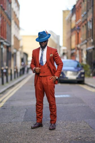 LONDON, ENGLAND - JANUARY 04: Edmond Kamara wears a blue hat with a feather, a white shirt, a blue tie, an orange blazer jacket, orange pants, purple leather shoes, a watch, during London Fashion Week Men's January 2020 on January 04, 2020 in London, England. (Photo by Edward Berthelot/Getty Images)