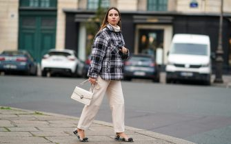 PARIS, FRANCE - NOVEMBER 29: Maria Rosaria Rizzo wears earrings, a black and white checked pattern puffer winter Parosh coat, a white wool turtleneck pullover, white Twinset pants, a Bulgari bag, flat shoes from Tory Burch, on November 29, 2020 in Paris, France. (Photo by Edward Berthelot/Getty Images)