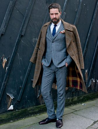 LONDON, ENGLAND - JANUARY 6: Model Jack Guiness wears a Top Man suit, Lee Man Paris hoes, Paul Smith socks, Aquascutum tie, D.S Dundee Jacket and a Silk and Favours Pocket Square  day 1 of London Mens Fashion Week Autumn/Winter 2014, on January 06, 2014 in London, England. (Photo by Kirstin Sinclair/FilmMagic)