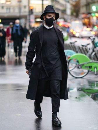 PARIS, FRANCE - OCTOBER 02: A guest wears a black face mask, a black hat, a black long coat, a white shirt, a long pullover, black pants, leather shoes, outside Yohji Yamamoto, during Paris Fashion Week - Womenswear Spring Summer 2021, on October 02, 2020 in Paris, France. (Photo by Edward Berthelot/Getty Images)