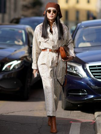 MILAN, ITALY - FEBRUARY 21: Yoyo Cao wears a brown hat, sunglasses, a jumpsuit, a brown leather belt, a brown leather bag, brown leather boots, outside Etro, during Milan Fashion Week Fall/Winter 2020-2021 on February 21, 2020 in Milan, Italy. (Photo by Edward Berthelot/Getty Images)
