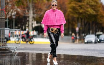 PARIS, FRANCE - OCTOBER 01: Sofie Valkiers wears sunglasses, earrings, a pink tweed jacket, a pink short cape, a Chanel belt-bag, shiny black patent leather pants, white pointy heels, outside Chanel, during Paris Fashion Week - Womenswear Spring Summer 2020, on October 01, 2019 in Paris, France. (Photo by Edward Berthelot/Getty Images)