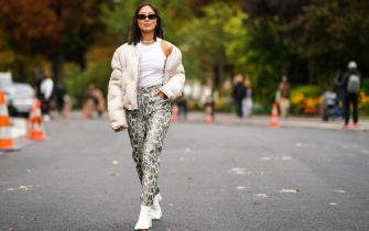 PARIS, FRANCE - SEPTEMBER 25: Aimee Song wears sunglasses, a white puffer jacket, a white sleeveless tank top, snake print pants, white shoes, outside Margiela, during Paris Fashion Week - Womenswear Spring Summer 2020, on September 25, 2019 in Paris, France. (Photo by Edward Berthelot/Getty Images)