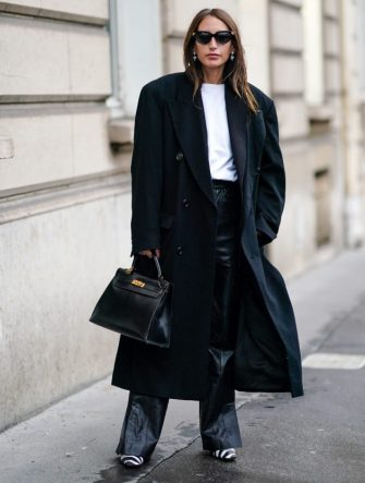 PARIS, FRANCE - FEBRUARY 28: Chloe Harrouche wears sunglasses, an oversized long coat, a white t-shirt, black leather flared pants, black and white zebra print pointy shoes, a black leather bag, earrings, outside Alessandra Rich, during Paris Fashion Week - Womenswear Fall/Winter 2020/2021, on February 28, 2020 in Paris, France. (Photo by Edward Berthelot/Getty Images)