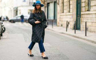 PARIS, FRANCE - OCTOBER 08: Therese Hellström wears a blue hat from Bronte, a black quilted Chanel bag with golden chain, a black padded puffer long coat from Custommade, blue denim  Custommade jeans, black pointy Custommade shoes, on October 08, 2020 in Paris, France. (Photo by Edward Berthelot/Getty Images)