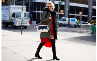 Zanita Whittington wears vintage sunglasses, a Mr & Mrs Italy green parka with a fur hood, a red Zimmermann robe-style dress, a Tod's wave bag, and Kurt Geiger boots during New York Fashion Week: Women's Fall/Winter 2016 on February 12, 2016 in New York City.
