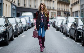 PARIS, FRANCE - SEPTEMBER 26: Alexandra Lapp wearing an oversized college jacket in leather from Set Fashion, a plaid shirt with studs from Set, high waist skinny jeans by Rag and Bone, Milla Tote bag with studded outlines in rustic brown from MCM, Les Specs sunglasses, and overknee boots in burgundy by Zara is seen during Paris Fashion Week Spring/Summer 2018 on September 26, 2017 in Paris, France. (Photo by Christian Vierig/Getty Images)