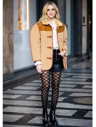 MILAN, ITALY - FEBRUARY 22: Chiara Ferragni, wearing a beige jacket with fur collar, white shirt, black leather shorts, checked tights and black boots, is seen outside Philosophy di Lorenzo Serafini show, during Milan Fashion Week Fall/Winter 2020-2021 on February 22, 2020 in Milan, Italy. (Photo by Claudio Lavenia/Getty Images)