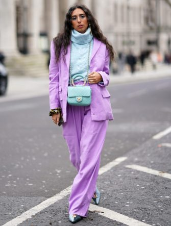 LONDON, ENGLAND - FEBRUARY 17: Gabriella Berdugo wears earrings, a pale blue wool oversized turtleneck pullover, an oversized pale purple blazer jacket, a quilted Chanel bag, flared large pants, pointy shoes, during London Fashion Week February 2020 on February 17, 2020 in London, England. (Photo by Edward Berthelot/Getty Images)