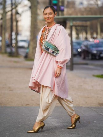 PARIS, FRANCE - MARCH 03: Jenny Walton wears a Chanel bag, a pink long jacket, flowing pants, golden shiny pointy shoes, a bejeweled shirt, earrings, outside Chanel, during Paris Fashion Week - Womenswear Fall/Winter 2020/2021 on March 03, 2020 in Paris, France. (Photo by Edward Berthelot/Getty Images)