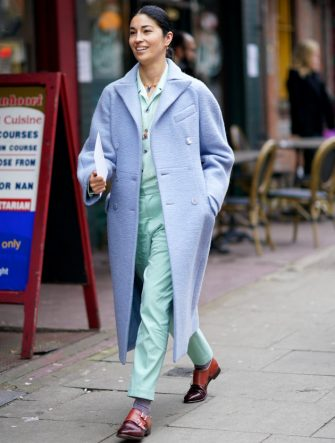 LONDON, ENGLAND - FEBRUARY 17: Caroline Issa wears a pastel pale blue coat, a green shirt, green pants, leather pointy shoes, during London Fashion Week February 2020 on February 17, 2020 in London, England. (Photo by Edward Berthelot/Getty Images)