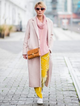 DUESSELDORF, GERMANY - DECEMBER 08: Gitta Banko wearing a pink cashmere turtleneck sweater with cut-outs on the shoulders by The Mercer NY, yellow velvet trousers by Mango, light-pink cashmere coat by Bruno Manetti, Stan Smith sneakers by Adidas, MCM cross-body bag, gold Y ring with watermelon tourmaline and diamonds and rose gold ladies watch by York Watches, sunglasses by Ray Ban on December 8, 2017 in Duesseldorf, Germany. (Photo by Christian Vierig/Getty Images)