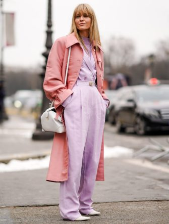 PARIS, FRANCE - MARCH 01:  A guest wears a pink trench coat, purple pants , during Paris Fashion Week Womenswear Fall/Winter 2018/2019, on March 1, 2018 in Paris, France.  (Photo by Edward Berthelot/Getty Images)