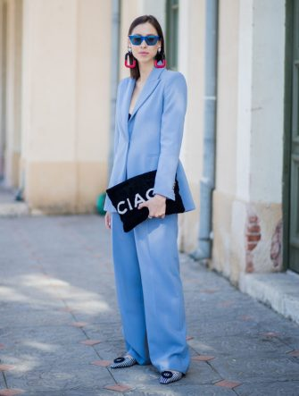 TEL AVIV, ISRAEL - MARCH 13: Romy Spector wearing blue Zara suit, Celine sunglasses, statement earrings, Balenciaga clutch is seen during Tel Aviv Fashion Week on March 13, 2018 in Tel Aviv, Israel. (Photo by Christian Vierig/Getty Images)