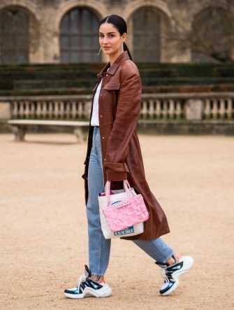 PARIS, FRANCE - JANUARY 20: Fiona Zanetti, wearing a white t-shirt, blue jeans, Louis Vuitton sneakers, pink Kenzo bag and brown long coat, is seen in the streets of Paris after the Kenzo show on January 20, 2019 in Paris, France. (Photo by Claudio Lavenia/Getty Images)