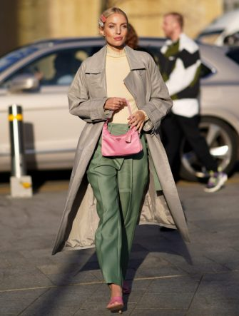 LONDON, ENGLAND - FEBRUARY 17: Leonie Hanne wears hair pins, a pale yellow pullover, a gray trench coat, green pants, a pink Prada fanny pack bag, pink shoes, during London Fashion Week February 2020 on February 17, 2020 in London, England. (Photo by Edward Berthelot/Getty Images)